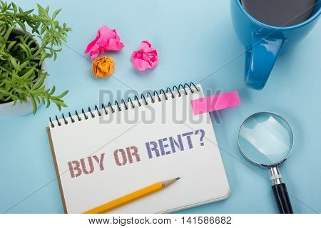 Real estate concept. Notepad with buy or rent message, coffee cup, pen and flower. Office supplies on desk table top view.