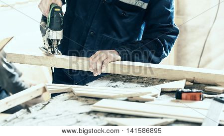 Sawing wooden log by fretsaw indoors. Construction concept