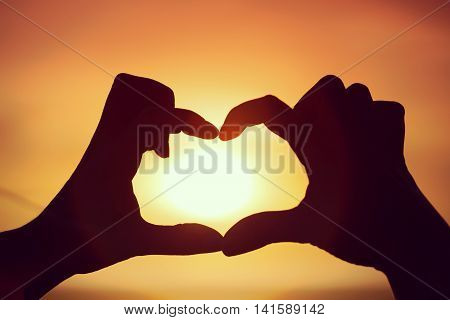 Silhouette Of Hand In Heart Shape With Sun In The Middle