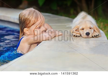 Funny photo of little baby swimming in blue outdoor pool look at lazy retriever puppy. Children water sports activity and swimming lessons training dogs fun games with family pet on summer vacation.