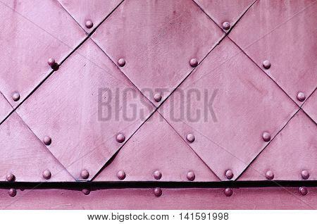 Metal grunge background in light pink colors - textured steel superficies of old carved metal plates with small rivets above.