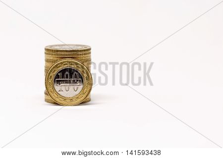 Bahrain 100 fils coins piled up and isolated on a white background
