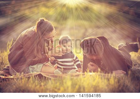Happy Familly With Their Kid In The Park In Warm Sunny Rays