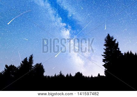 A view of the stars of the Milky Way with a silhouette of a pine trees forest in the foreground. Falling stars. Perseid Meteor Shower in 2016.