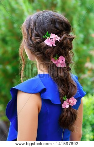 elegant hairstyle with fresh flowers in a plait . Woman with fashion wedding hair on nature background. Hairstyle. Wedding, flower decorations in the hair of the bridesmaid