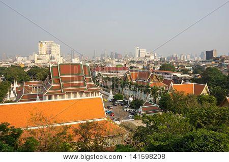 BANGKOK THAILAND - JANUARY 25 2015: Panoramic view of buildings of Bangkok and part of Wat Saket from top of Golden Mount in Bangkok Thailand