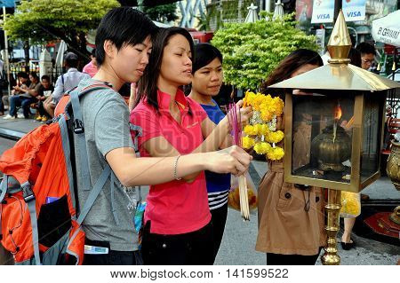 Bangkok Thailand - December 16 2011: Thais lighting incense sticks from a brass lantern while carrying orange Marigold floral tributes at the revered Erawan Shrine
