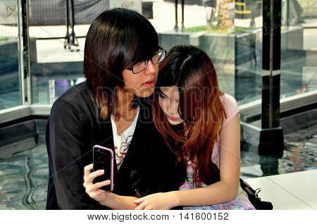 Bangkok Thailand - January 23 2013: Teenage girl with her boyfriend takes a selfie with her cellphone in the entrance atrium of the Siam Paragon Shopping Center