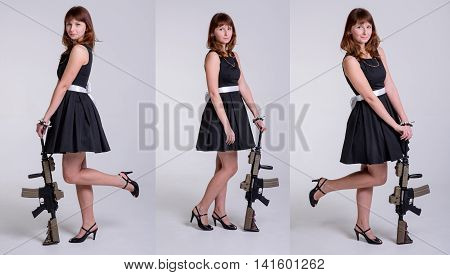Young cute girl in black dress posing with gun on white background