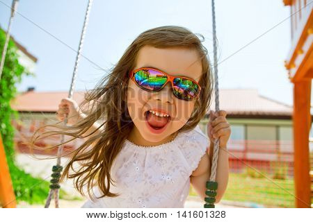 Happy girl in bright rainbow glasses swinging on a swing