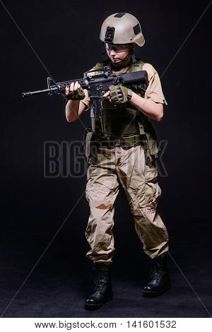 Young girl in uniform and helmet with gun on dark background