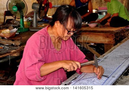 Chiang Mai Thailand - December 25 2012: Craftswoman carefully hammers out a stencil design over a sheet of tin in the artisan workshop at Wat Sri Suphan
