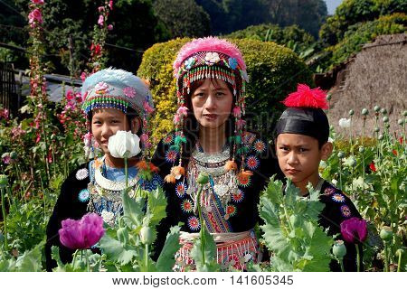 Doi Poi Thailand - December 24 2006: Thai family wearing traditional hilltop village clothing visiting a garden of opium Poppies and Hollyhocks