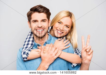 Happy Cheerful Man Carrying His Girlfriend On The Back And Showing Two Fingers