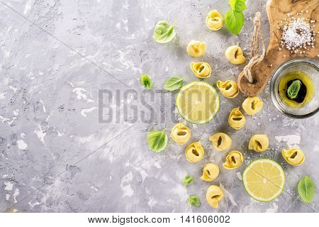 Italian tortellini with olive oil, balsamic sauce, basil, lime on a gray concrete background. Ingredients for a traditional home dinner. Top view