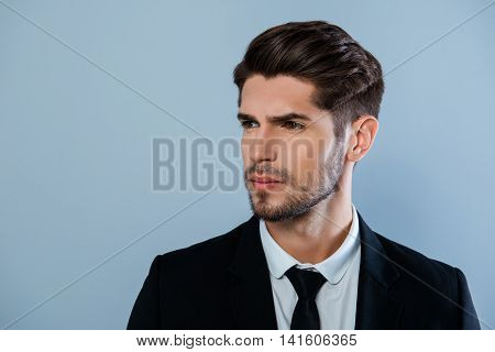 Portrait Of Handsome Harsh Man With Bristle In Black Suit