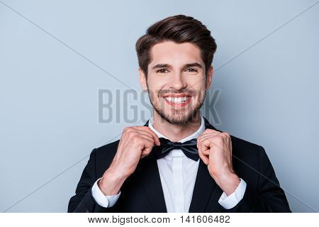 Cheerful Handsome Man With Beaming Smile Corecting His Bow Tie