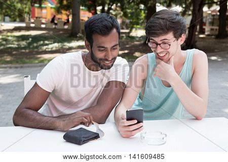 Two multicultural men sitting at the park and using phone