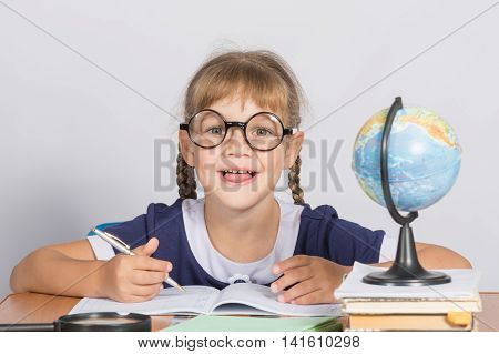 Happy First Grader Sits At A Table In The Classroom, With His Mouth Open In Pleasure