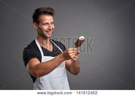A handsome young barista man smiling and offering an ice-cream