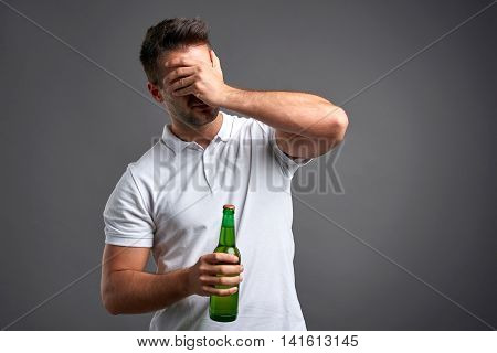 A handsome young man feeling desperate and grabbing his head while holding a beer