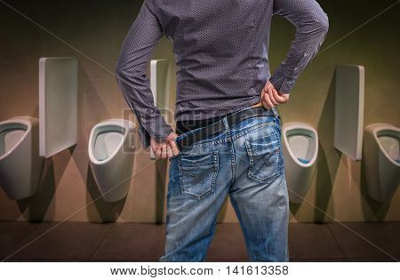 Standing Man Peeing To A Urinal In Restroom