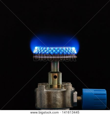 Propane gas burner with blue Bunsen flame. Used for stoves and in laboratory for heating, sterilization, and combustion. The device generate an open flame and safely burns a continuous stream of gas.