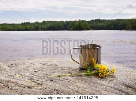 Stainless steel mug with yellow flowers on stone near water on nature background