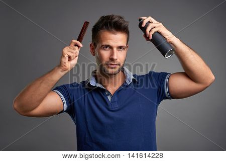 A handsome young man smiling while holding a comb and a hairspray in his hand.
