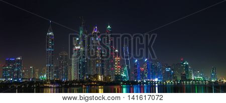 Dubai sity skyline at night and skyscrapers view. View of the Dubai Marina and Jumeirah Islands. Skyscrapers with night illumination
