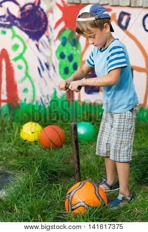 Boy Inflates Soccer Ball Pump