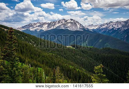 Aspen Twin Valleys summer landscape deep valley and High Mountains in Colorado June Pine Tree forests with some snow on top