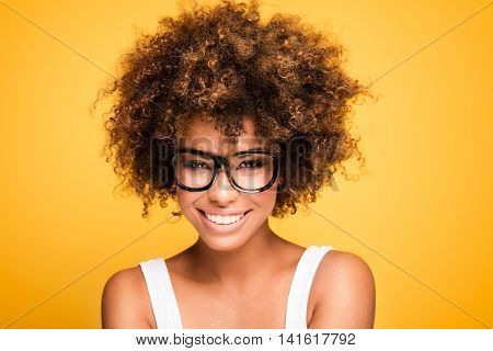 Young beautiful african american girl with an afro hairstyle. Laughing girl wearing eyeglasses. Portrait. Yellow background. Girl looking at camera. poster