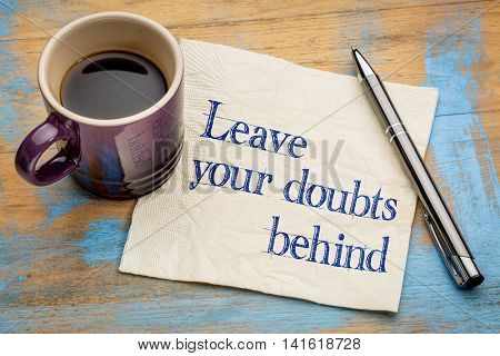 Leave your doubts behind - handwriting on a napkin with a cup of espresso coffee