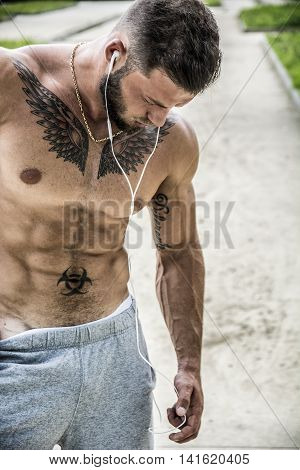 Handsome Muscular Shirtless Hunk Man Listening to Music with Earphones. Outdoor in City Setting. Showing Healthy Body While Looking away