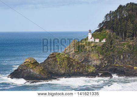 Coastal view of Heceta head lightstation in Yachats, Oregon with crashing waves and moss rocks