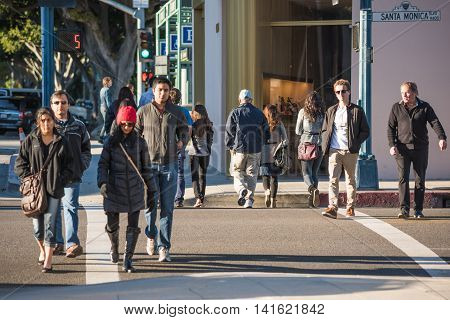Los Angeles, USA - December 25, 2015: Pedestrians crossing the famous Santa Monica boulevard during winter bundled up with coats
