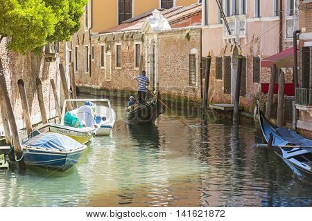 VENICE,ITALY-AUGUST 12,2014:Venetian gondoliers carry around some tourists on a gondola in Venice During a sunny day inside her famous canals.