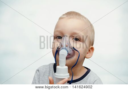 Child making inhalation with mask on his face. Asthma problems concept