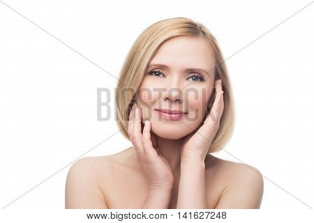 Beautiful middle aged woman with smooth skin and short blond hair touching her face. Beauty shot. Isolated over white background. Copy space.