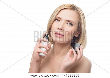 Beautiful middle aged woman with smooth skin and short blond hair applying face serum. Beauty shot. Isolated over white background. Copy space. poster