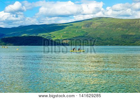 Tourists on canoe on calm blue Loch Lomond lake in Luss Scotland, 21 July 2016
