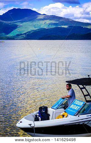 Man on the tour motor boat at the Loch Lomond lake in Scotland, 21 July 2016