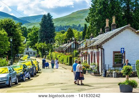 People walking in the street along beautiful stone cottages in Luss Scotland UK, 21 July 2016