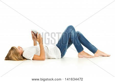 Young girl lying on the floor using tablet pc over white background