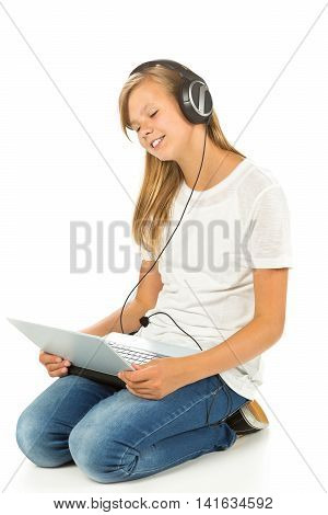 Young girl lying on the floor listening to music on her laptop over white background