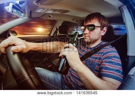 Man driving the car and drinking beer
