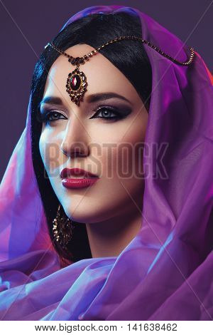 Beautiful young caucasian woman with long black hair and arabian style makeup. Vintage accessory on head. Purple fabrics. Studio shot over dark background. Copy space.