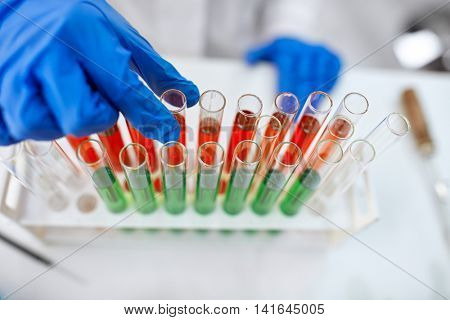 Scientist hand holding a laboratory glass test tube filled with red end green liquid