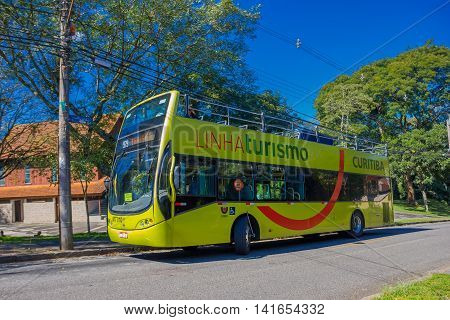 CURITIBA , BRAZIL - MAY 12, 2016: green bus tour waiting on the stop parked in the street next to some trees.